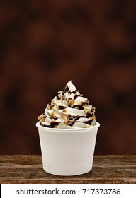 Chocolate sauce, sorbet, syrup, sherbet and hazelnut / filbert sundae or frozen custard in white blank paper or cardboard cup on wooden table with brown background