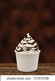 Chocolate sauce sundae or frozen custard in white blank paper or cardboard cup on wooden table with brown background