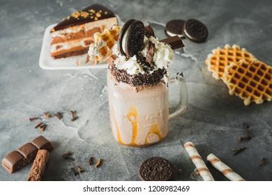 Chocolate shake with dripping sauce, cream, cookies and cake