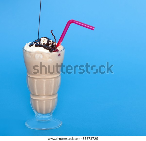 Chocolate shake with a drizzle of chocolate sauce on a blue background