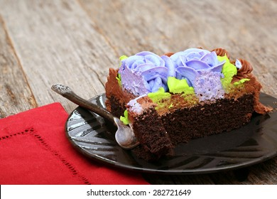 Chocolate sheet cake covered with chocolate icing on a plate with a fork