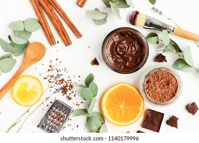 Chocolate skincare mask. Natural ingredients for making beauty treatment products. Cacao, orange slices, aroma oil, jars and spoons, herbal leaves. Top view white table.