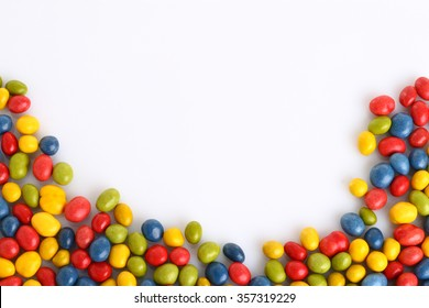 chocolate smarties shaping lower part of picture on white with copy space