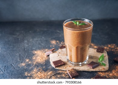 Chocolate smoothie with banana, decorated with mint leaf on the dark background with pieces of chocolate and cocoa powder. Healthy diet food. Selective focus, space for text