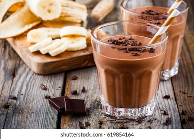 Chocolate smoothie with banana on rustic wooden background