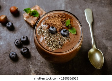 Chocolate smoothie with blueberry, nuts and chia seeds on a grey background