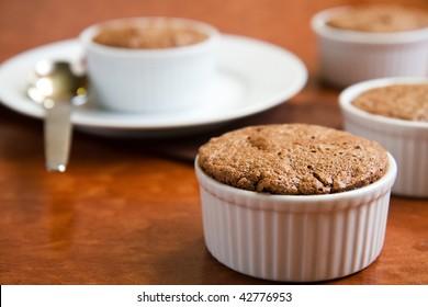 Chocolate souffles in ramekins garnished with cherries