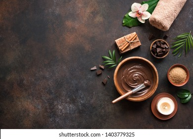 Chocolate Spa flat lay on dark background, top view, copy space. Natural chocolate spa beauty products with towel and plants.