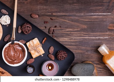 Chocolate spa set on the wooden background, top view. Body care essentials, aroma oils and other