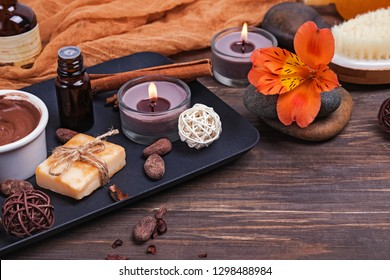 Chocolate spa set on the wooden background, close-up. Body care essentials, aroma oils and other