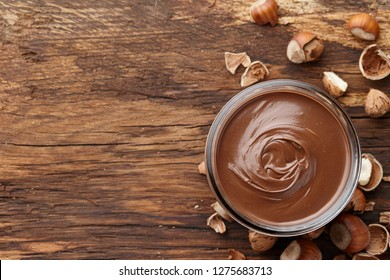 Chocolate spread or nougat cream with hazelnuts in glass jar on wooden background, top view