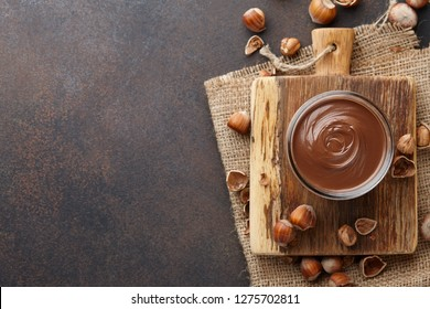 Chocolate spread or nougat cream with hazelnuts in glass jar on brown textured countertop, copy space