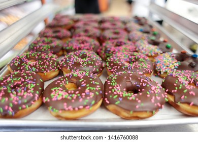 Chocolate sprinkle donuts on racks at the donut shop.