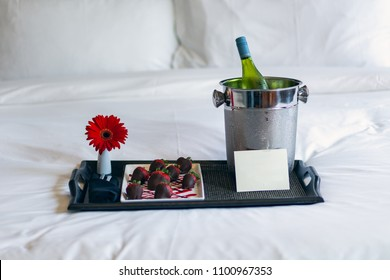 Chocolate strawberries with champagne/wine on bed