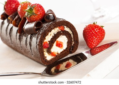 Chocolate and strawberry gateaux with serving slice, reflection of cake in cutter