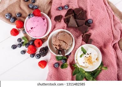 Schokolade Erdbeere Vanilla Eis Set flach Lay. Drei verschiedene Eiscreme-Dessert im Cup Top Down View. Brauner weißer und rosafarbener Gelato Farbmix. Sortenartiges Set mit weichem, gefrorenem, cremefarbenem Snack