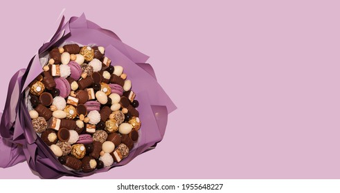 Chocolate Sweet candy bouquet on lilac purple background. Assortment of chocolate colourful, festive sweets candy lilac macaroons and nuts. Birthday, Mother's Day, Women Day, Valentine's Day card.