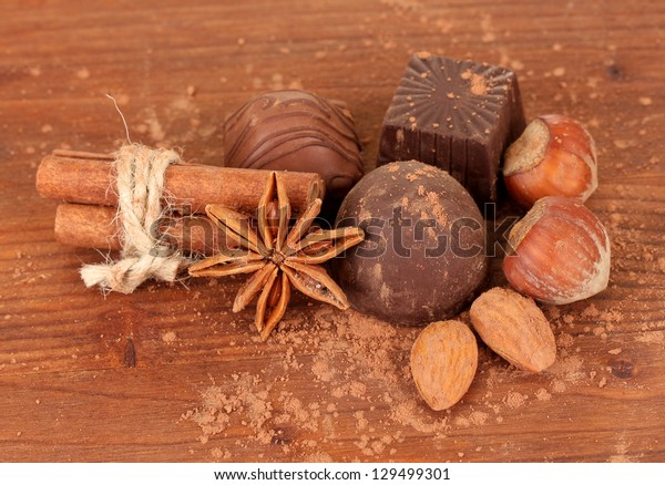 Chocolate sweets with cocoa,spices and nuts on wooden background