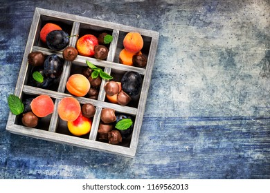Chocolate sweets with dried fruits and fresh fruits in wooden box. Blue concrete background. place for text.