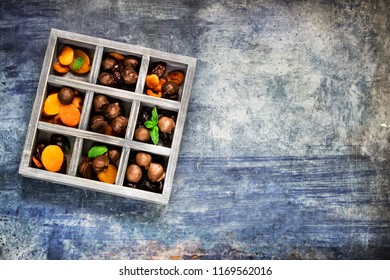Chocolate sweets with dried fruits and in wooden box. Blue concrete background. place for text.