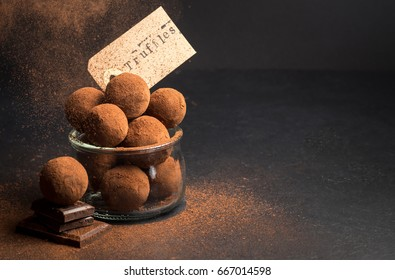 Chocolate sweets truffle in a jar with pieces of chocolate and flying cocoa powder on a dark background
