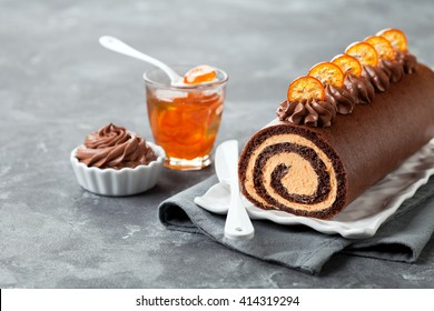 Chocolate swiss roll cake with candied kumquats, selective focus