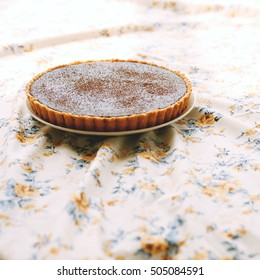 chocolate tart on a floral table cloth
