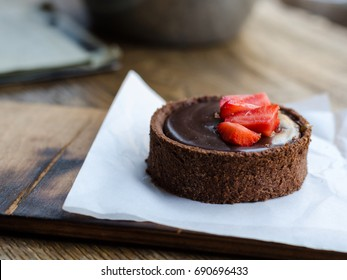 Chocolate tart with salted caramel, decorated with pieces of fresh strawberries.