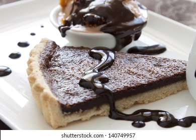 Chocolate tart slice and ice cream with melted dripping chocolate sauce.
