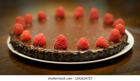 Chocolate torte dessert with fresh raspberries on a white plate and farmhouse table