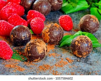 Chocolate truffle, raspberry and mint. The concept of a chocolate-raspberry dessert. Chocolate truffles and ripe raspberries.