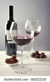 Chocolate truffles and glasses with red wine on white wooden table