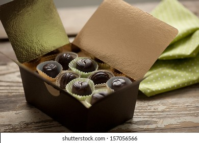 Chocolate truffles in gold gift box, rural atmosphere