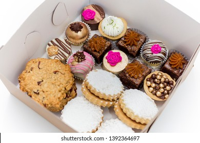 Chocolate truffles, mini brownies, white and dark chocolate bonbons, alfajores, and delicious cookies in a gift white box on a white background