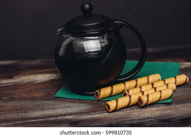 Chocolate tubes, coffee in a mug on a green napkin, teapot