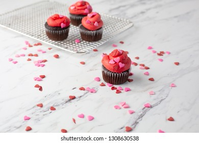 Chocolate Valentines Cupcakes on Wire Rack decorated with Heart-Shaped Sprinkles; One Isolated in Front on Red Heart-shaped Doily; Heart-shaped Sprinkles on White Marble Countertop