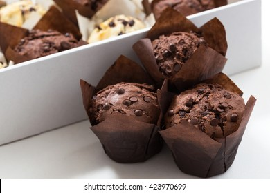 Chocolate and vanilla muffins, paper muffins holder, muffins box, selective focus, close up