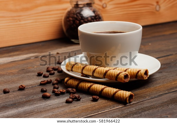 chocolate wafer rolls on a saucer, coffee, teapot.