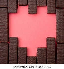 chocolate wafers are laid out in the form of heart on a red background