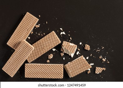 Chocolate wafers whole and broken on old black metal background, top view with place for text