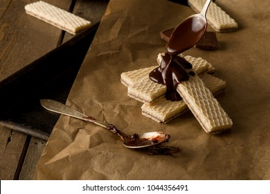 Chocolate waffers on the parchment and a wooden background