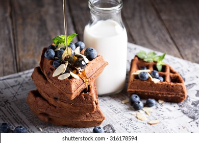 Chocolate waffles with milk and berries for breakfast
