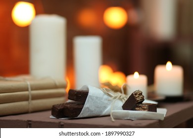 Chocolate waffles on a background of white candles.