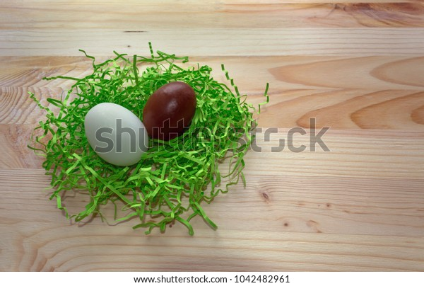 chocolate and white egg in green nest on wooden background