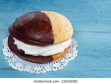 Chocolate whoopie pie on blue rustic wooden background