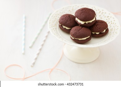 Chocolate whoopie pies with buttercream filling on cake stand