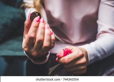 Chocolate in woman's hands, opening chocolates. A woman holds in her hand a chocolat, a blank, worn out chocolatier, eating chocolate, obesity, unhealthy eating, sweet food.