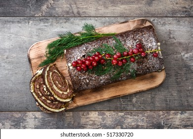 Chocolate yule log christmas cake with red currant on wooden background.copyspace