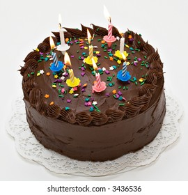 Chocolate-lover's birthday cake with lit candles.