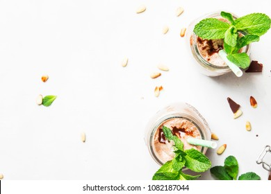 Chocolate-mint milkshake with pine nuts, gray background, top view